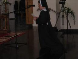 Siostra, klęcząc przed ołtarzem, składa dozgonne śluby zakonne.